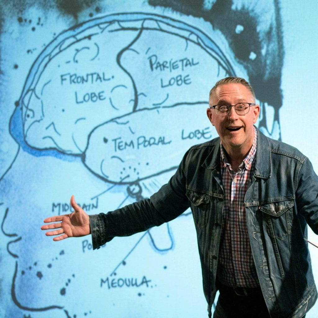 Portrait of William Doan in front of a drawing of a brain