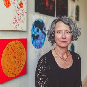 portrait of Deirdre Murphy with paintings in background